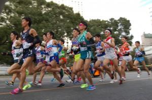 JR品川駅前の渋谷稲門会応援団の前を通過する1区のトップ集団。